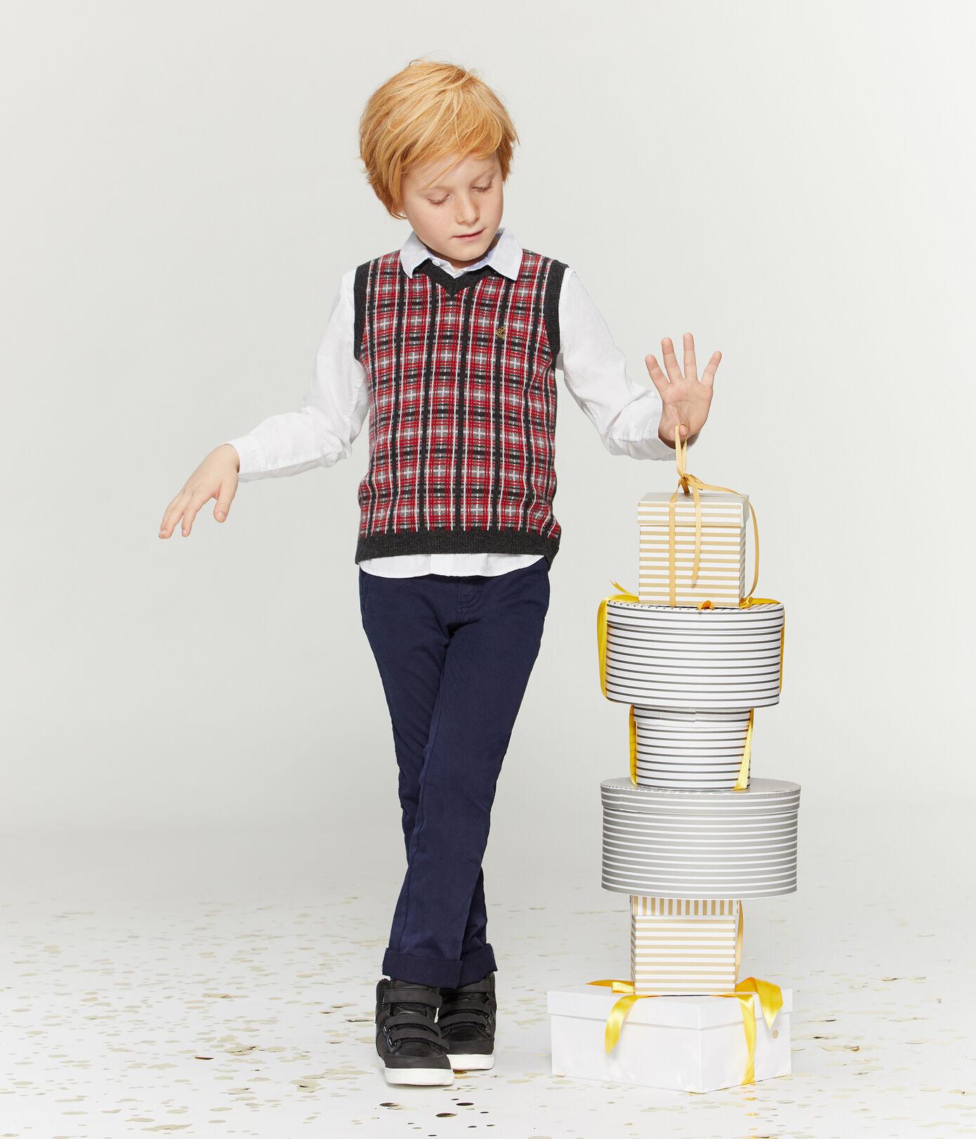Petit garçon en tenue de fête composée d'un pantalon, d'une chemise et d'un pull sans manche