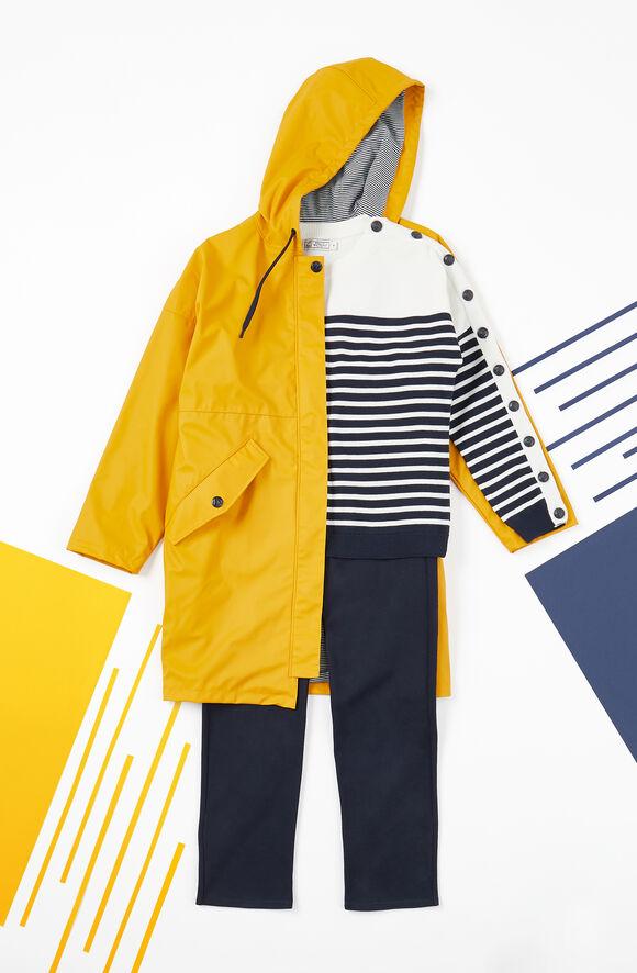 Look marin avec un ciré jaune pour femme, un pull marinière et un pantalon droit noir.